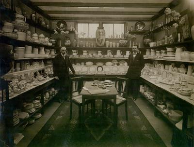 Image from object titled Het interieur van een showroom, geflankeerd door twee medewerkers.