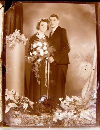 Image from object titled Anoniem, glascliché huwelijksportret van jong echtpaar, in decor met bloemen, s.d.