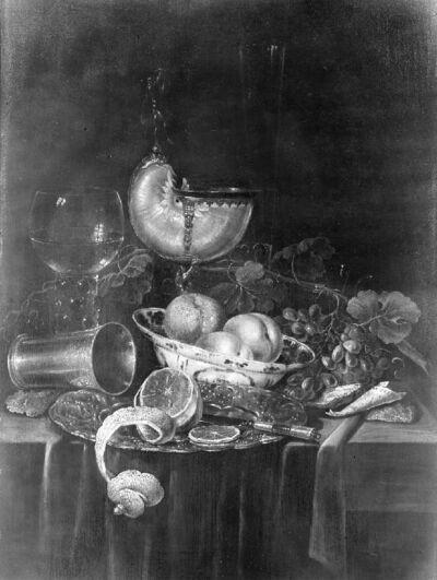 Stilleven met nautilusbeker, een roemer wijn, een Wan Li-kom, oesters en een omgevallen zilveren beker
