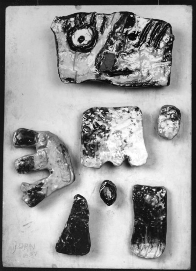 Sept pièces de céramique sur une plaque en plâtre (personnage)