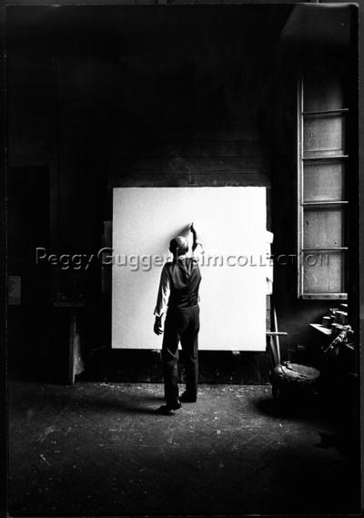 Fotografia dell'artista mentre taglia una tela di Ugo Mulas.