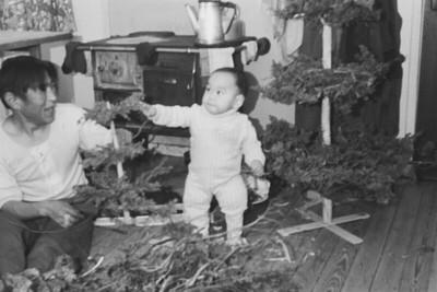 Image from object titled Lars Jonathansen bezig met de vervaardiging van een kerstboom. Zijn zoontje Mozessie kijkt toe. Kerstbomen worden in Tinitegilaq gemaakt van een bezemsteel waaraan een groen afkomstig van een Juniperus soort, tussen jeneverbessoort wordt vastgespijkerd. Wie een kerstboom wil maken met kerstmis zal daarvoor in september eigenlijk maatregelen moeten nemen. In het geval van de boom van Lars gebeurde dat ook. In september twrwijl er al veel nieuw ijs op de fjord lag voeren wij op een keer door het ijs heen en verzamelden op een plaats waar we eerst zalm gevangen hadden, een grote hoeveelheid takken van deze jeneverbes. Ik begreep toen nog niet waarvoor ze gebruikt zouden worden, maar Lars nam ze mee naar huis en legde ze bij z???n huis, waar ze aldra door de sneeuw worden bedekt. Tegen kerstmis 1967 begon hij in de sneeuw te graven tot hij de takken terug gevonden had die eruit zagen of ze zojuist geplukt waren. Deze takken werden met spijkers en hamer op een bezemsteel vast getimmerd en zo had Lars een kerstboom gemaakt. Hij maakte er in totaal 4. Een voor zijn gezin en een voor zijn jongste zoontje Mozessi, Vervolgens nog twee te weten een voor ons gezin en voor onze kleinste Jeroen Nooter. Er waren toen het kerstmis was vrij veel kerstbomen in Tiniteqilaq, maar de meeste jagers hadden natuurlijk vergeten in september, of uiterljk in oktober, de takken van de jeneverbes te verzamelen zodat ze het zonder moesten doen