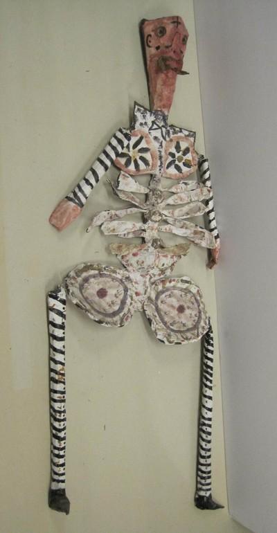 Uit papier-maché??? vervaardigde skeletpop met roze hoofd en handen. De pop is versierd in roze, blauw, zwart, goud en geelgroen.