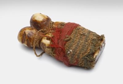 Twee uit been gesneden, ruggelings aan elkaar gebonden talismannen, omkleed met groene en rode stof. De schedeldoek is doorboord.