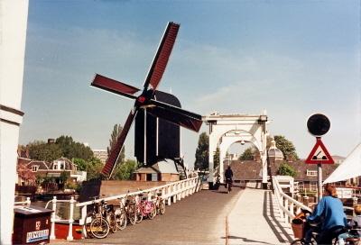 """Molen """"De Put""""te Leiden, op molendag 9 mei 1987. Molen maalt met vier volle. Foto is genomen vanaf de Rembrandbrug."""