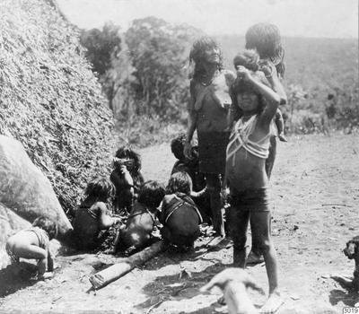 Motiv: Kvinnor och barn utanför hydda. Lokal: Uazirimi, R.Jauru, Brasilien. Stam: Paressi-Kabisi. Foto av: Max Schmidt. Dato: 1910. Erh.: av dito. (katalogkort); 003019; Sydamerika