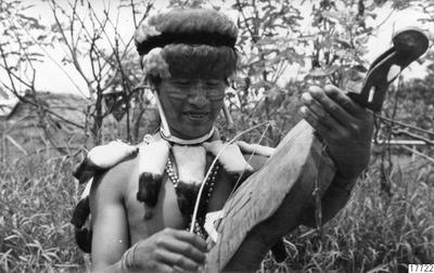 "Motiv: ""Achual with violin"". Fotos from Wong´s Amazon Tours via ""Galeria de arte primitivo de la Amazonia"" med brev 19 okt. 1968. Lokal: Övre R.Pastaza, Peru. Stam: ""Achual"". Foto: Wong, 19 okt 1968. Erh: till arkivet,..."