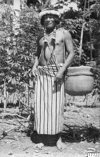 """Motiv: """"Achual with double woven basket they keep their feathers in called in called petakas."""" Fotos from Wong´s Amazon Tours via """"Galeria de arte primitivo de la Amazonia"""" med brev 19 okt. 1968. Lokal: Övre R.Pastaza,..."""
