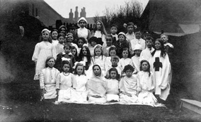Image from object titled A group of children in fancy dress. They are probably taking part in an event organised by the Misses Hinks to raise money for missionary charities. They seem to be dresses as World War One nurses...