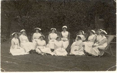 Group of nurses sat in garden. 'Nurse Cockroft seated next to Sister', 1914-1919.