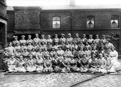 Image from object titled Women and girls on war work at E. Green & Sons, Calder Vale Road. The woman in the centre with a large hat must have been a supervisor, all the others were on the production line. Munitions work...