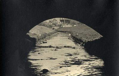 Image from object titled Doorkijk onder de brug over de Grift bij de Julianastraat richting de brug van de Christiaan Geurtsweg. De vervuiling is goed te zien.