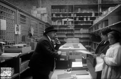 """PAUL POIRET (1879-1944), COUTURIER ET DÉCORATEUR FRANÇAIS, À L'USINE DE PARFUMS """"ROSINE"""". COURBEVOIE, VERS 1930."""