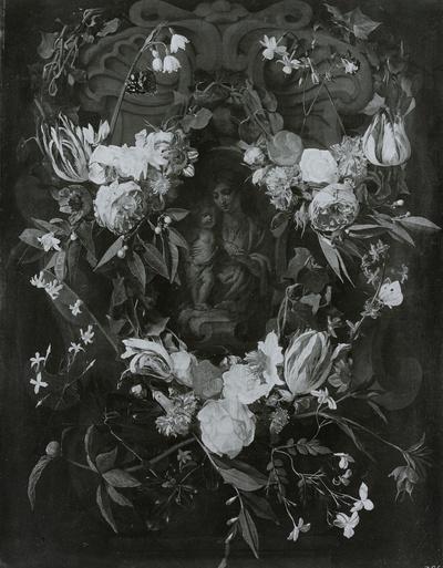 Blumen um ein Steinrelief der Maria mit dem Kinde