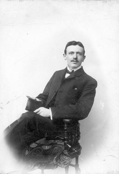 Porträt Richard Heinrich, auf einem Stuhl sitzend und einen Zylinder haltend, aufgenommen im Photoatelier in Hamburg, Wandsbeker Chaussee 191