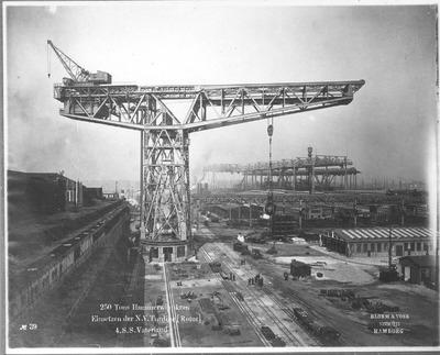 """Hochseepassagierdampfer """"Vaterland"""" am Ausrüstungskai der Bauwerft Blohm und Voß. Einsetzen der Turbine (Rotor) per ortsfestem 250-Tonnen-Hammerwippkran"""