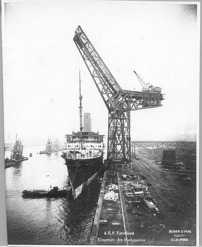 """Hochseepassagierdampfer """"Vaterland"""" am Ausrüstungskai der Bauwerft Blohm und Voß. Einsetzen des vorderen Mastes (Fockmast) per ortsfestem 250-Tonnen-Hammerwippkran"""