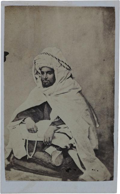 Home assegut amb turbant i capa