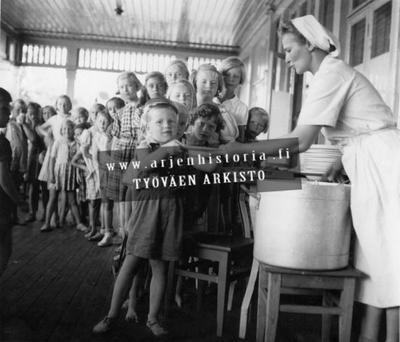 Lapsia kesäsiirtolan ruokajonossa. Keittäjä jakaa ruokaa. 1950-luku
