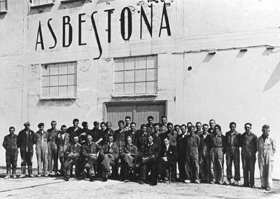Image from object titled Een grote groep mannen in overall staat voor het witte hoofdgebouw. Voor deze groep mensen zitten zes mannen op een rij, vijf gekleed in een overall en de man rechts in een pak met overhemd,...