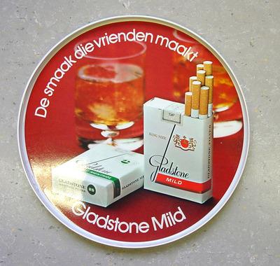 """Rond dienblad met een witte onderkant en rand. Op de bovenkant staan twee sigarettenpakjes afgebeeld van """"Gladstone Mild"""" en """"Gladstone Mild Mentol"""" met daarachter twee glazen met drank en de tekst """"De smaak die vrienden..."""