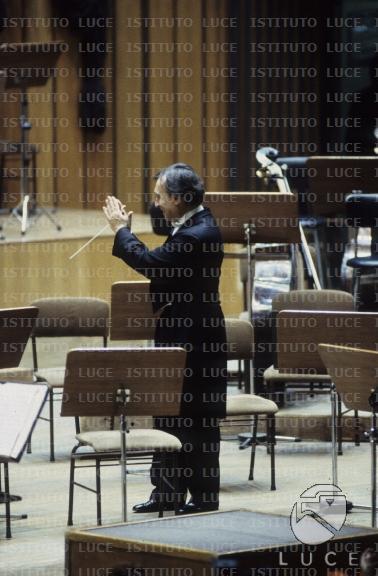 Claudio Abbado, di spalle, ringrazia tenendo la bacchetta tra le mani tra i banchi d'orchestra vuoti