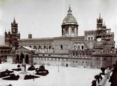 Veduta del fronte meridionale della Cattedrale di Palermo con scorcio della piazza antistante. Spicca il bel portico gotico. In piazza alcune aiuole attorno al monumento a Santa Rosalia