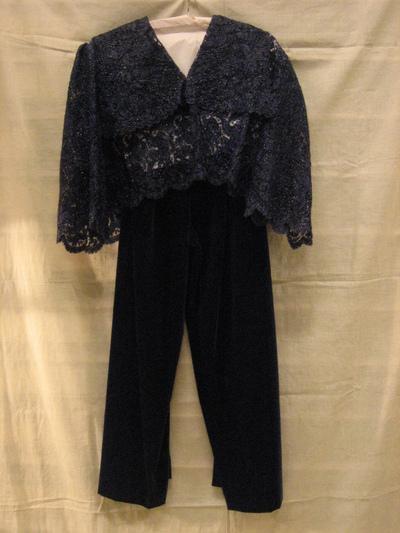 Avondensemble bestaande uit blouse van nachtblauw machinaal kant doorweven met raffia en lange broek van blauw fluweel