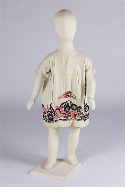 Jurk (meisje) van crèmekleurig linnen met borduursels langs de onderzijde in wol in zwart
