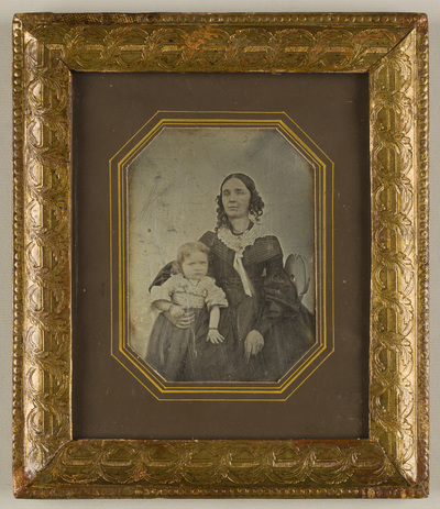 Image from object titled compare the counterpart GF-3966; Portrait of a woman sitting on a chair and holding a child at her right side
