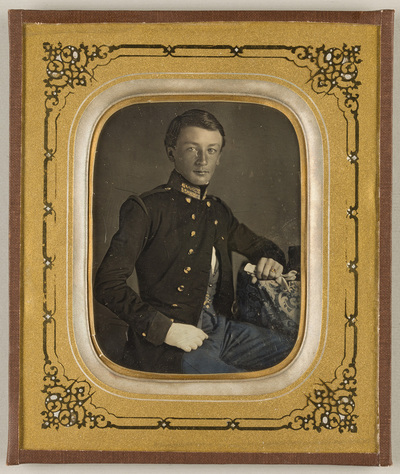 Image from object titled Portrait of a young man in uniform, seated, resting his left arm on a table, in left hand holding a white glove. The tablocloth is decorated with floral and ornamental motif.