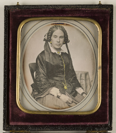 Image from object titled Case adjustable as a stand; Portrait of a woman with a plait, seated. A small table depicted fuzzily in the background .