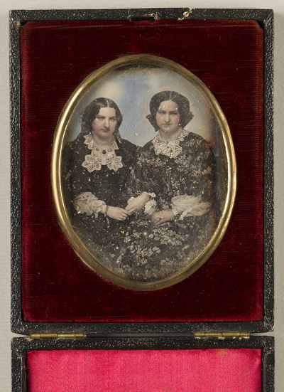 Image from object titled Casette adjustable as a stand; Portrait of two young women seated, holding each other´s hand. Their sleeves and collars are lavishly decorated with laces. Their cheeks and hands are coloured in red.