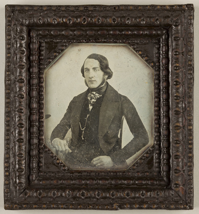 Image from object titled Possibly produced by the Prague studio of Wilhelm Horn, dated 1841 p.q., Voigtländer - Petzval camera plate.; Portrait of a man, sitting on a chair, resting his right arm on a table. The tablecloth...