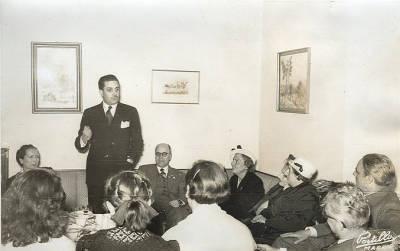 1952. Viatge a Madrid. Grup de deu persones escoltant les paraules de Francisco Sintes, Director General de Archivos y Bibliotecas
