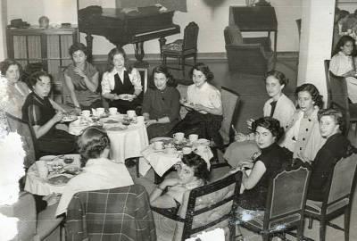 1952. Viatge a Madrid. Grup de dotze noies prenent cafè i pastes