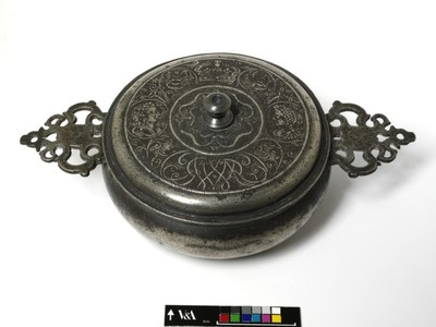Pewter porringer decorated on the cover and inside the base with a cast design of flowers and portrait busts. English, late 17th century.
