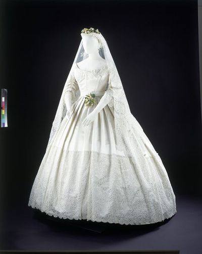 Image from object titled White satin and Honiton lace wedding dress.   Silk-satin, trimmed with Honiton appliqué lace, machine net and bobbin lace, hand-sewn.