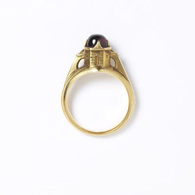 Cabochon almandine garnet set in a gold ring in the form of a turret or castle. Designed by Charles Ricketts and possibly made by Carlo Giuliano, England, 1899-1903. The gold setting is high, in the form of a turret or...