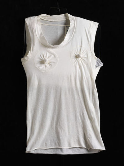 Sleeveless cotton T-shirt, designed by Malcolm McLaren and Vivienne Westwood, Great Britain, 1981.  Sleeveless white cotton T-shirt with two bobble knots of fabric over the nipples. Cotton.