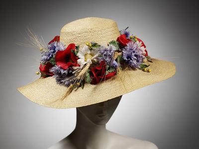 Image from object titled Natural straw broad-brimmed hat trimmed with fabric flowers and wheat. Natural straw broad-brimmed hat with fabric poppies, cornflowers, daisies, and wheat stalks.Straw.