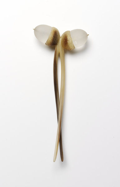 Decorative hair comb in the form of paired acorns, by Martin Baker England 1980.  Horn and crystal.