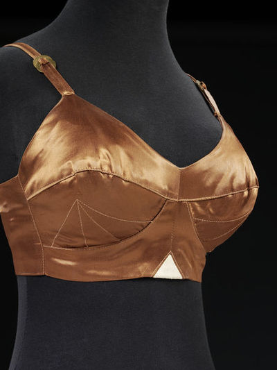Bra of brown synthetic satin, cotton and leather; United Kingdom, 1982.
