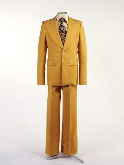 Men's suit in yellow wool, designed by Victor Herbert, Great Britain, 1974.  Men's suit of yellow wool comprising of jacket and trousers. Trousers of yellow wool with flared legs, 2 front hip pockets, with hook and eye...
