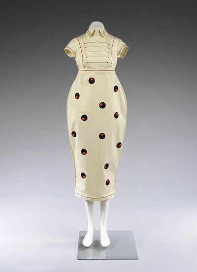 Dress, cream cotton with orange circle print, by Willy Brown, Great Britain, 1980. Dress, three-quarter length, with collar, in cream cotton with orange and black stripes on bodice and back of skirt, and orange circle...