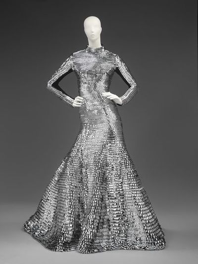 Dress, with neckpiece, metallic silver vinyl, designed by Gareth Pugh, Britain, 2011. Full length fitted evening dress of tabbed silver vinyl. The dress has long sleeves and is fitted from the neck to the thigh where the...