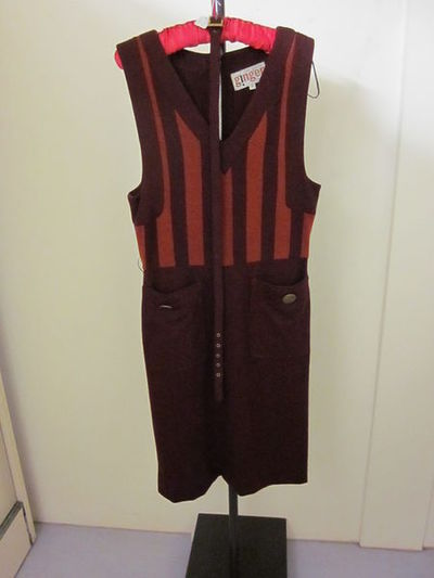 Pinafore dress and belt of jersey, designed by Mary Quant, made in England, 1967-1968.Pinafore dress and belt. Dark maroon wool jersey with wide stripes of burnt-orange on the vest-style top, back zipper.Jersey.