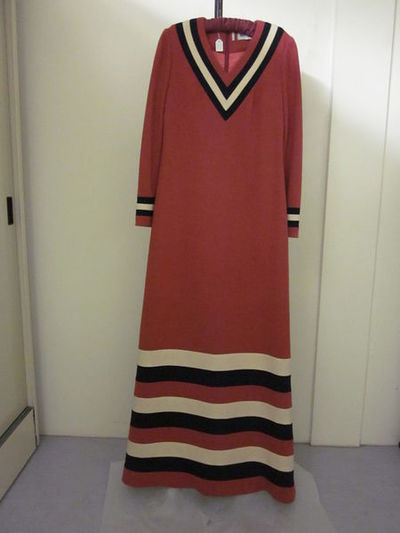 Dress of jersey, designed by Mary Quant, England, 1964, 1973 replica.Evening dress of deep rust-pink wool jersey. It is full length with deep V-neck trimmed with black and cream stripes round neckline, cuffs and hem. It...