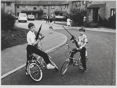 Image from object titled 'Brothers in Arms 1987' black and white photographic print of two boys facing each other, each astride his bicycle and holding a toy gun; taken by John Heywood in the UK, 1987.Photographic paper...