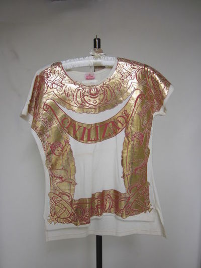 Cotton T-shirt with gold appliqué.White cotton T-shirt with gold appliqué on front. The back is slightly longer than the front.Cotton and plastic appliqué.
